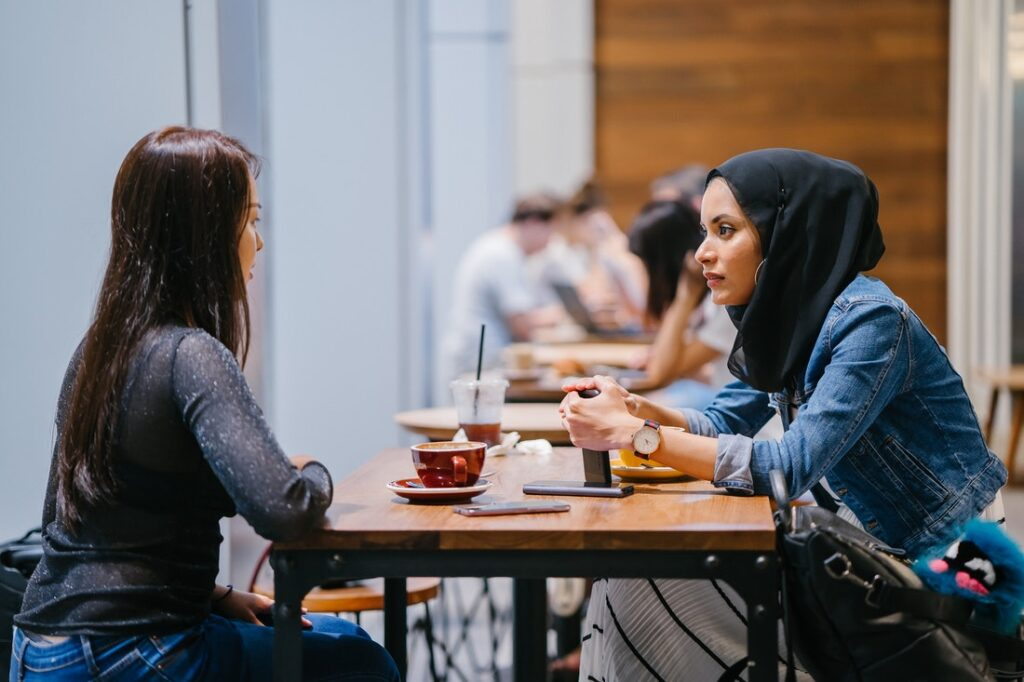 two women talking in a cafe setting