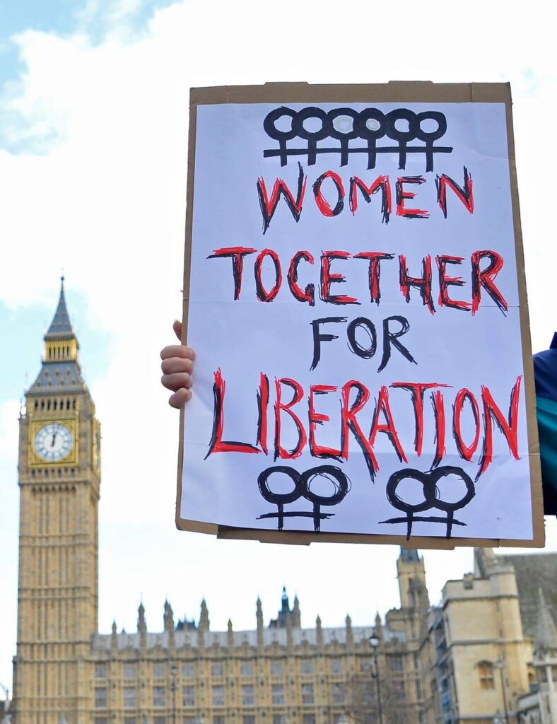 Women together for liberation poster held in front of the Houses Of Parliament